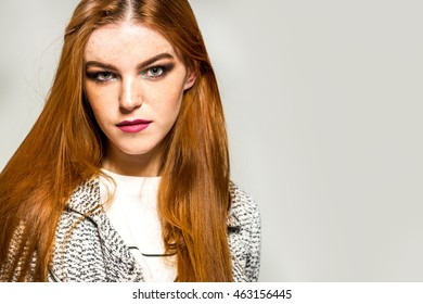 Beautiful woman with straight red hair against gray foil background