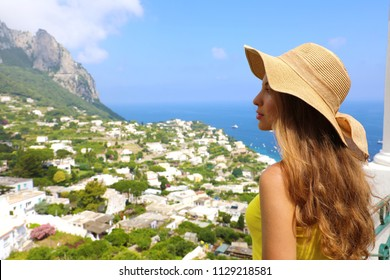 Beautiful woman with straw hat looking at Capri sight from terrace, Capri Island, Italy