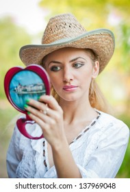 beautiful woman with straw hat and mirror .Young woman looking in cosmetic mirror .Good looking beautyfull  woman doing make-up in front of mirror.