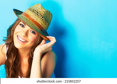 beautiful woman with straw hat smiling and happy . blue background .