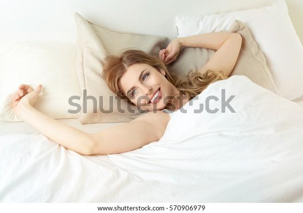 Hermosa mujer que se estira con los brazos por la mañana en su cama.