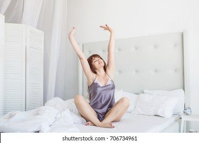 Beautiful woman stretching in bed sitting in lotus pose. White bed. American.