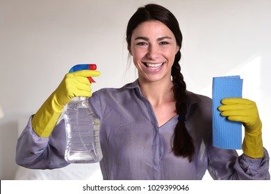 A beautiful woman struggling with house cleaning cleans the glass with a spray and a cloth on purpose. Concept of: cleaning, perfection, domestic crafts, cleaning products.