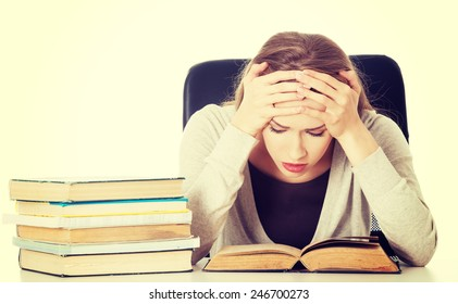 Beautiful woman student worried with stack of books.