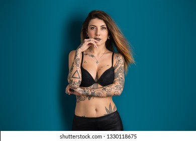Beautiful woman studio portrait with tattoo against blue background.