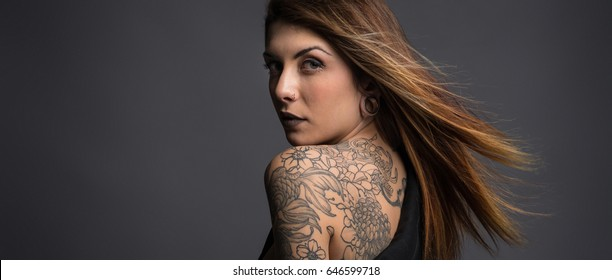 Beautiful woman studio portrait with tattoos on her shoulder.