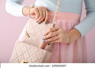 Schöne Frau mit stilvollem Accessoires und ParfüFlasche auf Farbhintergrund, Nahaufnahme