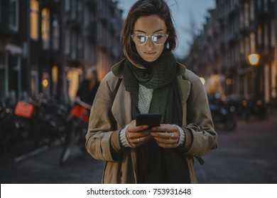 Beautiful woman in stylish coat typing an sms message to her family while walking at night city streets, young hipster girl wearing vintage glasses and using modern smartphone outside