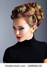 Beautiful woman with a stylish hairstyle. Fashion model with multicolor hair - posing at studio