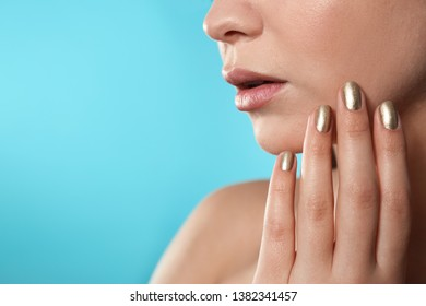 Beautiful woman with stylish nail polish on color background, closeup. Space for text
