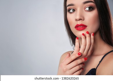 Beautiful woman with stylish nail polish on grey background, space for text