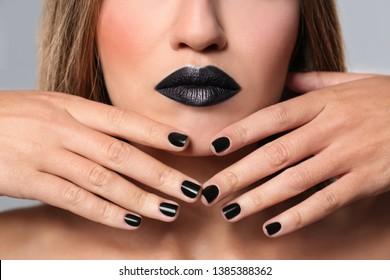 Beautiful woman with stylish nail polish on grey background, closeup