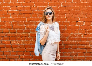 Beautiful woman in stylish vintage white blouse with denim jacket. On the background of red brick wall