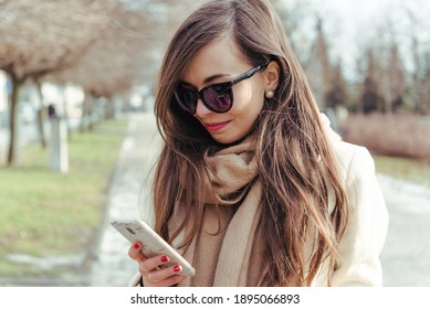 Beautiful woman in stylish winter outfit checking messages on the smartphone