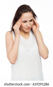 Beautiful woman suffering of a headache and massaging her temples, isolated on white