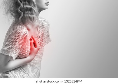 Beautiful woman suffering from pain In chest. Health Issues. Breast pain (cancer), heart pain concept, isolated on grey background. Heart attack. Copy space for text.