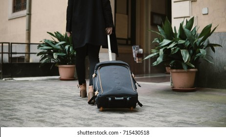 Beautiful woman with suitcase going away from apartment. Businesswoman with baggage are going to trip, vacation.