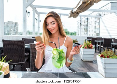 Beautiful woman summer cafe, sitting table restaurant. Happy smiling resting work lunch or dinner. Pays plastic credit card, online application, online banking. Smile enjoyment, quick money transfer.