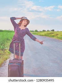 Beautiful woman in summer dress and hat hitchhiking with baggage on the road. Woman thumb up and stands with suitcase. Travel concept