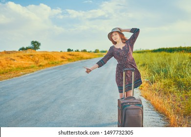 Beautiful woman in summer dress and hat hitchhiking with baggage on the road at fall. Cool female hitchhiker thumb up and stands with suitcase. Hitchhike concept