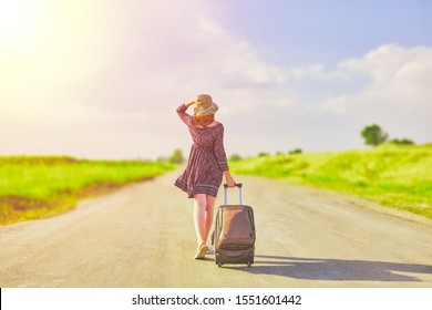 Beautiful woman in summer dress and hat hitchhiking with suitcase at spring. Female walking on the road with baggage at sunny day. Hitchhiker concept