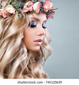 Beautiful Woman with Summer Pink Flowers. Blonde Beauty. Long Permed Curly Hair and Fashion Makeup. Beauty Girl with Flowers Hairstyle, Closeup Portrait