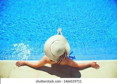Beautiful woman in sun hat taking sun bath near swimming pool.