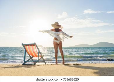 Beautiful woman sunbathing in a bikini on a beach at tropical travel resort enjoying summer holidays