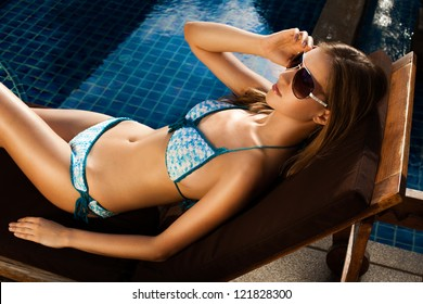 Beautiful woman sunbathing in chair near pool outdoors