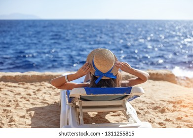Beautiful woman sunbathing on a beach at tropical travel resort, enjoying summer holidays. Young woman lying on sun lounger near the sea. Happy serene woman