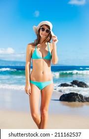 Beautiful woman in sunhat and bikini at the beach