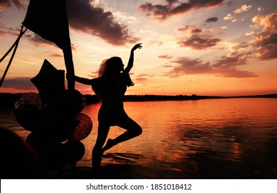 Beautiful Woman at the sunset on the boat on the river in Thailand. amazing silhouette of a woman with air balloons and copy space. travel, holidays concept