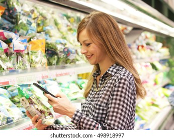 Beautiful woman at supermarket using mobile in fresh sala area. Shopping mobile app concept. Checking ingredients. Capturing food code.