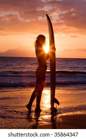 beautiful woman with surfboard standing at tropical sunset
