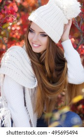 Beautiful woman in a sweater in the fall. Fall concept - autumn woman drinking coffee on park bench under fall foliage. Portrait of smiling woman wearing woolen accessories