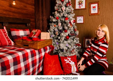 beautiful woman in a sweater poses before a Christmas tree in New Year's interior