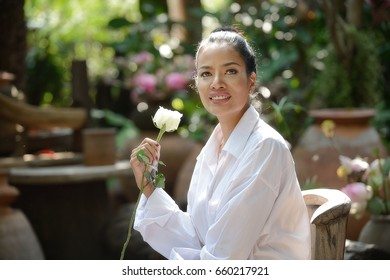 Beautiful woman with sweet Valentine's white roses in holding while sitting in the Bali garden.