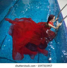 Beautiful woman swimming underwater with elegant dress