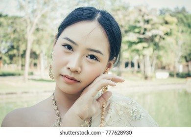 Beautiful Woman take a Thai traditional Dress , Pretty Girl Standing in the Garden.