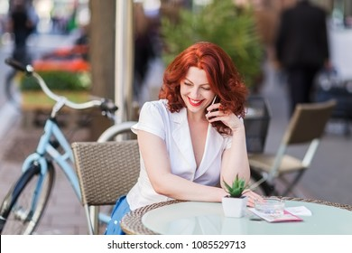 beautiful woman takes a phone call while sitting in a street cafe