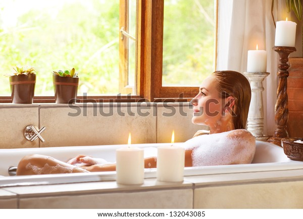 Beautiful woman taking bath at home, cute female lying down in bathtub, warm candle light, romantic atmosphere, pampering and hygiene, spa resort in hotel, zen balance concept