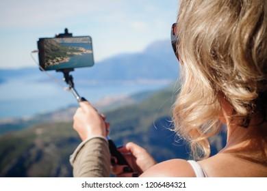 Beautiful woman taking panoramic picture of summer mountain landscape. Selfie photo stick. Zabljak Durmitor, Montenegro