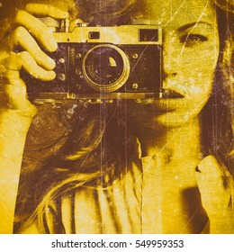 Beautiful woman taking photos with retro film camera. Close up. Old grungy texture. Golden concrete wall.