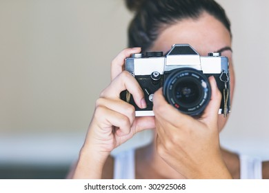 Beautiful woman taking pictures with a film camera
