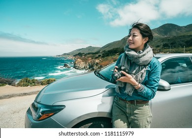 beautiful woman taking pictures for the stunning view and leaning her body on a car.