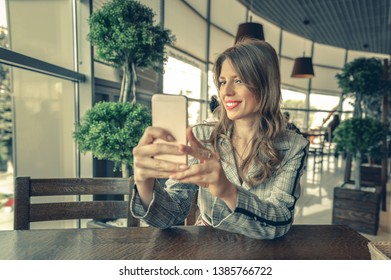 beautiful woman taking selfie in a cafe. lovely woman uses her phone as a mirror. Young girl at restaurant taking self portrait