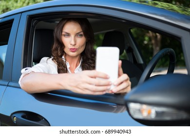 Beautiful woman taking selfie with mobile phone in car