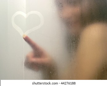 Beautiful woman taking a shower and drawing heart on the sweat and blurred glass.
