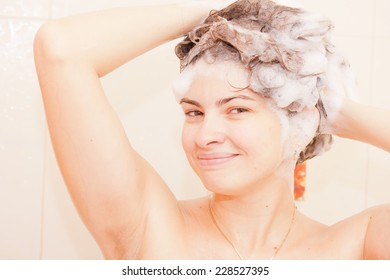 Beautiful woman taking a shower and shampooing her hair.