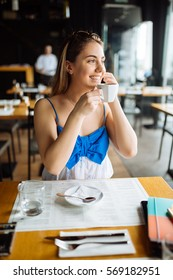 Beautiful woman talking on cell phone and drinking coffee